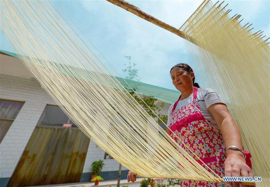 A villager dries handmade hollow noodles in Wangqing Village, Handan City of north China's Hebei Province, June 12, 2018. Handmade hollow noodles increase the income of local people in Wangqing Village, where the making of the hollow noodles has a history of over 100 years. (Xinhua/Wang Xiao)