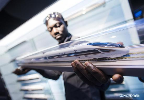 A railway executive from Ghana watches a model of Fuxing bullet train at a training base for high-speed railway staff in Wuhan, central China's Hubei Province, June 12, 2018. Altogether 63 railway executives from 13 countries including Thailand, Sri Lanka and Laos visited the training base Tuesday. (Xinhua/Xiao Yijiu)