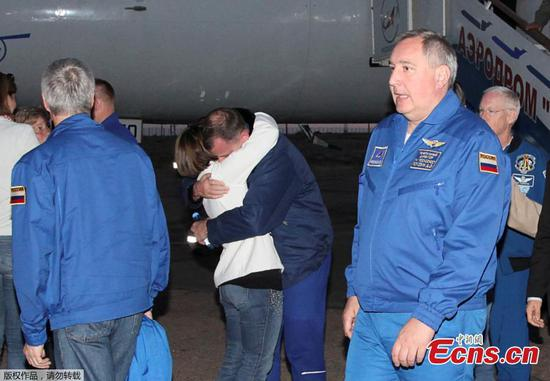 U.S. astronaut Nick Hague embraces a family member as head of the Russian space agency Roscosmos Dmitry Rogozin (R) walks past, after the Soyuz spacecraft made an emergency landing following a failure of its booster rockets, upon the arrival at Baikonur airport, Kazakhstan October 11, 2018. (Photo/Agencies)
