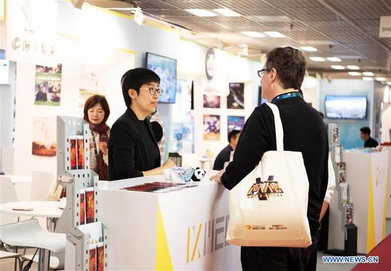People visit the Chinese booth during the 2019 Cannes International Series Festival, or Canneseries 2019, in Cannes, France, April 8, 2019. Many TV series, documents and cartoons presented by Chinese exhibitors drew people's attention during the big event running from 5 to 10 April. (Xinhua/Jack Chan)