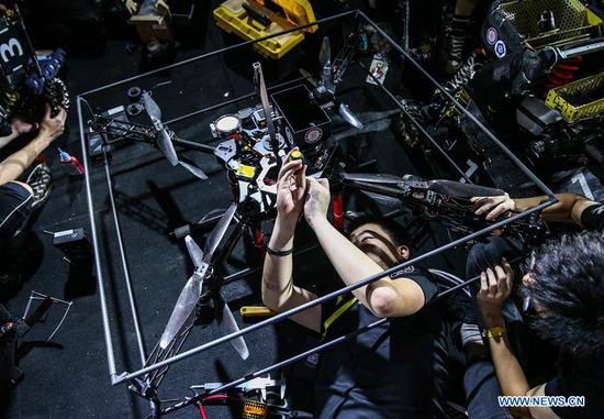 Participants test a robot during the finals of the 18th RoboMaster Robotics Competition in Shenzhen, south China's Guangdong Province, Aug. 6, 2019. The final tournament of the 18th RoboMaster Robotics Competition kicked off here on Tuesday, with 32 teams from home and abroad competing for the championship. (Xinhua/Jin Yu)