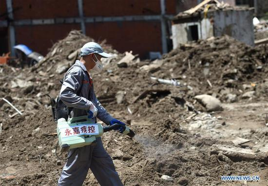 A worker sterilizes the landslide site in Shanzao Village of Yantan Township in Yongjia County, east China's Zhejiang Province, Aug. 12, 2019. By Monday morning, the death toll in Zhejiang Province has risen to 39 while nine others remained missing, said the Zhejiang provincial flood control headquarters. Typhoon Lekima, the ninth and strongest typhoon of the year, landed around 1:45 a.m. Saturday in the city of Wenling in Zhejiang Province. (Xinhua/Han Chuanhao)