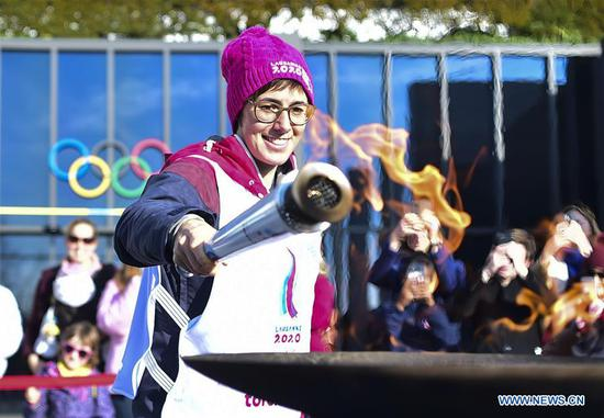 Torch bearer Linda Indergand lights up the cauldron during a torch relay for the 3rd Youth Winter Olympic Games in Lausanne, Switzerland, Jan. 8, 2020. (Xinhua/Lu Yang)