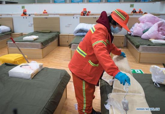 A worker puts an electric blanket on a bed at a temporary hospital converted from Wuhan Sports Center in Wuhan, central China's Hubei Province, Feb. 12, 2020. With the fundamental facilities being set up, the temporary hospital with a total of 1,100 beds is ready to admit patients with mild symptoms caused by the novel coronavirus. (Xinhua/Xiao Yijiu)