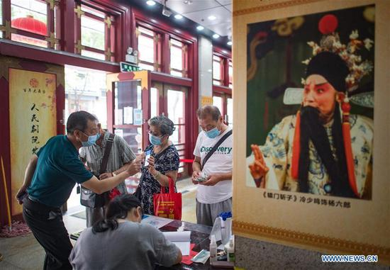 People make registrations before entering Renmin theater in Wuhan, central China's Hubei Province, June 26, 2020. Seven theaters reopened to the public on Friday in Wuhan. (Xinhua/Xiao Yijiu)