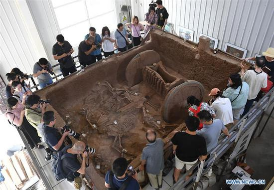 A restored bronze chariot is on display at a base of Shaanxi Provincial Institute of Archaeology in Xi'an City, northwest China's Shaanxi Province, July 30, 2020. A bronze chariot, dating from the Western Zhou Dynasty (1046-771 BC), has been restored by cultural-relics protection workers in a project lasting three years, according to the Shaanxi Provincial Institute of Archaeology. The chariot, unearthed in 2014 at the Zhouyuan site in northwestern Shaanxi, is 3.13 meters long, 2.7 meters wide, and 1.5 meters high. When it was discovered, it had been crushed into thousands of fragments. The skeletal remains of four horses were also unearthed with it. (Xinhua/Li Yibo)
