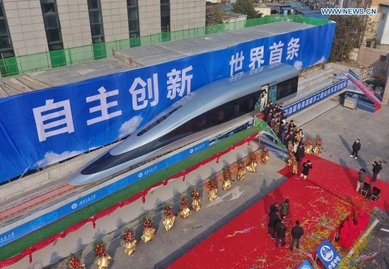 Aerial photo taken on Jan. 13, 2021 shows a maglev train prototype on the test line during a launch ceremony in Chengdu, southwest China's Sichuan Province. A prototype locomotive using high-temperature superconducting (HTS) maglev technology was rolled out on Wednesday in southwest China's city of Chengdu. The domestically developed maglev train boasts a designed speed of 620 kph, according to Southwest Jiaotong University, one of the train's designers. A 165-meter line to test the new train was launched on the same day. (Xinhua/Liu Kun)