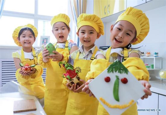 Children show smile signs made of vegetables and fruits to celebrate the World Smile Day at No. 1 Kindergarten in Shijiazhuang, capital of north China's Hebei Province, May 8, 2018. The World Smile Day is celebrated on May 8 every year. (Xinhua/Liu Peiran)