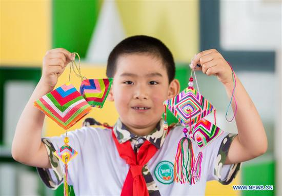 A pupil shows sachets in the shape of Zongzi, pyramid-shaped dumplings made of glutinous rice wrapped in bamboo or reed leaves, to greet the upcoming Dragon Boat Festival at a primary school in Hohhot, capital of north China's Inner Mongolia Autonomous Region, June 12, 2018. (Xinhua/Ding Genhou)