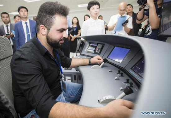 A railway executive from Jordan experiences a simulation of high-speed train driving at a training base for high-speed railway staff in Wuhan, central China's Hubei Province, June 12, 2018. Altogether 63 railway executives from 13 countries including Thailand, Sri Lanka and Laos visited the training base Tuesday. (Xinhua/Xiao Yijiu)
