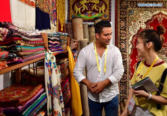 An exhibitor from India introduces scarfs to a visitor at the 20th China International Fair for Investment and Trade in Xiamen, southeast China's Fujian Province, Sept. 8, 2018. (Xinhua/Wei Peiquan)