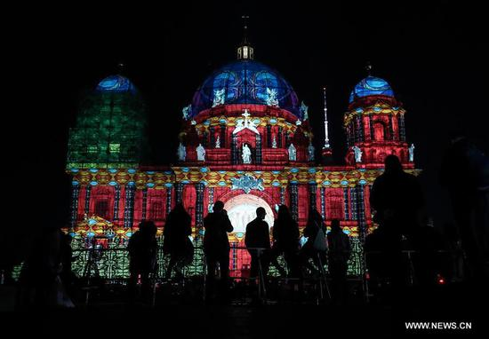 Silhouettes of visitors are seen against the illuminated Berlin Cathedral during the 2018 Festival of Lights in Berlin, capital of Germany, on Oct. 5, 2018. Berlin turned into a city of light art with the opening of its Festival of Lights on Friday which will last from Oct. 5 to Oct. 14. (Xinhua/Shan Yuqi)