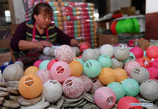 A worker makes paper lanterns at a factory in Jian'ou City, southeast China's Fujian Province, Nov. 4, 2018. Paper lanterns produced by local enterprises and workshops are now exported to markets in Europe, North America and Southeast Asia. (Xinhua/Zhang Guojun)