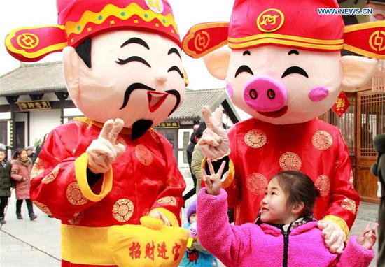 A child interacts with mascots at a scenic area in Huaibei, east China's Anhui Province, Feb. 7, 2019. (Xinhua/Zhou Fangling)