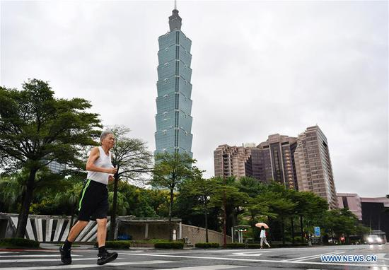 A citizen runs in front of the Taipei 101 skyscraper in Taipei, southeast China's Taiwan, on Oct. 1, 2019. Celebrations for the 70th anniversary of the founding of the People's Republic of China (PRC) will be held Tuesday in central Beijing. (Xinhua/Chen Bin)