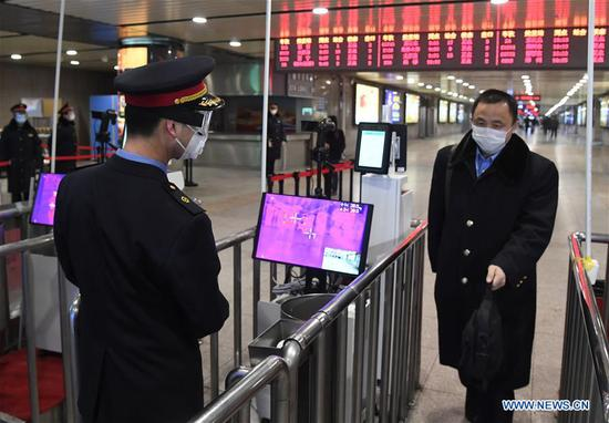 A staff member (L) checks a passenger's temperature at the exit of Beijing West Railway Station in Beijing, capital of China, Feb. 2, 2020. Chinese authorities have tightened measures to battle the novel coronavirus epidemic as a growing number of people hit the road and return to work after the Spring Festival holiday. (Photo by Ren Chao/Xinhua)