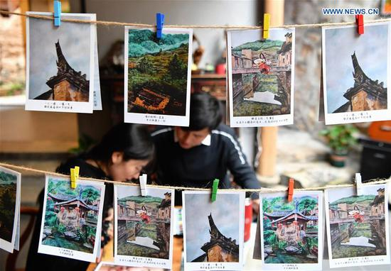 Photo taken on Oct. 21, 2020 shows the postcards made by Hu Wenliang, a professional designer introduced to Longtan Village who started a cultural and creative space here, together with his family, in Longtan Village of Pingnan County in Ningde City, southeast China's Fujian Province. Longtan Village had been a provincial-level poverty-stricken village due to lack of arable land. Villagers went out for work one after another with many old buildings left in disrepair. In 2017, the county government launched a project to boost ancient villages through cultural and creative industries. The old houses, once forgotten, have been connected to public utilities, reinforced and decorated inside, with the ancient appearance of the village remained. Moreover, the renaissance here has attracted many people and college graduates outside the village to work here. Nowadays, more and more people come to visit Longtan since the village has become popular on the Internet. (Xinhua/Wei Peiquan)