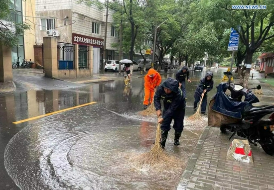 Photo taken with a mobile phone on July 18, 2021 shows community workers cleaning a waterlogged street after rainstorms hit Haidian District in Beijing, capital of China. The Beijing Meteorological Observatory on Sunday morning issued an orange warning for rainstorms after the accumulated rainfall in some areas of the capital had exceeded 150 mm. (Xinhua)
