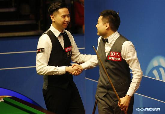 Xiao Guodong (L) of China shakes hands with his compatriot Ding Junhui after their first round match at the World Snooker Championship 2018 at the Crucible Theatre in Sheffield, Britain on April 24, 2018. (Xinhua/Craig Brough)