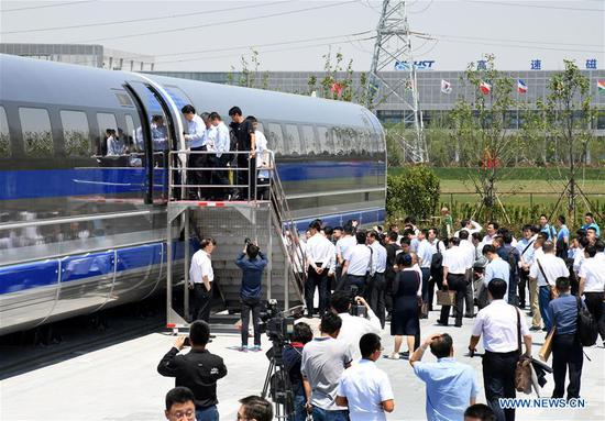 Guests visit China's first high-speed maglev train testing prototype in Qingdao, east China's Shandong Province,on May 23, 2019. China on Thursday rolled off the production line a prototype magnetic-levitation train with a designed top speed of 600 km per hour in the eastern city of Qingdao. The debut of China's first high-speed maglev train testing prototype marks a major breakthrough for the country in the high-speed maglev transit system. The engineering prototype is scheduled to roll off the production line in 2020 and go through comprehensive tests to finish integrated verification in 2021. (Xinhua/Li Ziheng)