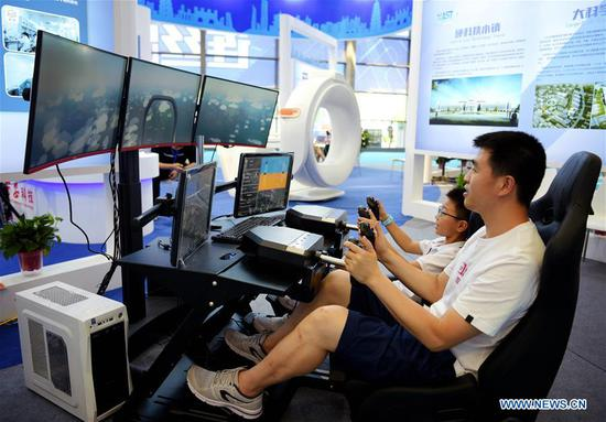 Visitors experience a flying simulator during the 14th China Xi'an International Science & Technology Industry Expo and Hard & Core Technology Industry Expo at Qujiang International Conference and Exhibition Center in Xi'an, capital city of northwest China's Shaanxi Province, Aug. 15, 2019. The expo opens on Thursday and will showcase fruits covering fields including artificial intelligence, aerospace, biological technology and information technology. (Xinhua/Liu Xiao)