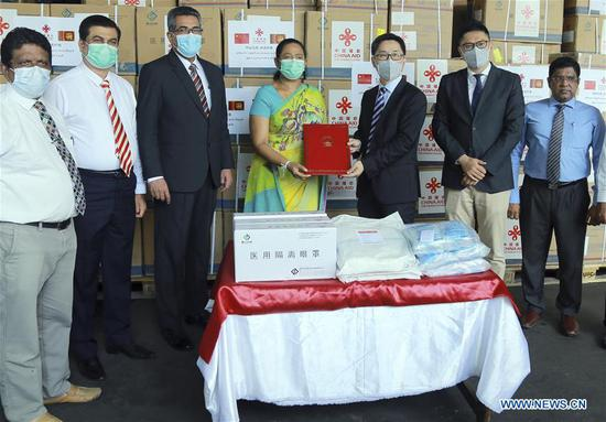 Hu Wei (3rd R), charge d'affaires of the Chinese Embassy to Sri Lanka, hands over the list of medical aid donated by China to Sri Lanka's Minister of Health Pavithra Wanniarachchi (4th L) at a handover ceremony in Colombo, Sri Lanka, June 24, 2020. China on Wednesday donated its third batch of medical aid to Sri Lanka to help the country fight the COVID-19 virus which has to date infected over 2,000 people in the country and caused 11 deaths. (Photo by Ajith Perera/Xinhua)