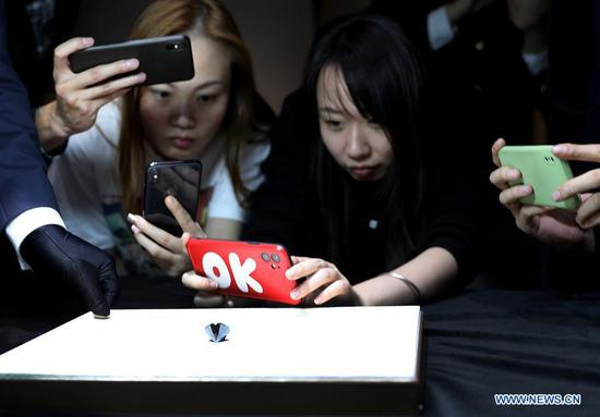 Media workers take pictures of a black diamond weighing 88 carats in Shanghai, east China, Oct. 26, 2020. With an estimated value of 37 million U.S. dollars, the diamond from Paris will be on display during the upcoming third China International Import Expo (CIIE) in Shanghai. (Xinhua/Fang Zhe)