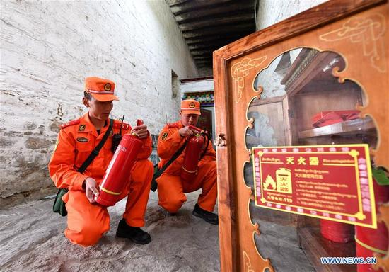 Firefighters check fire extinguishers during an emergency drill at the Potala Palace in Lhasa, southwest China's Tibet Autonomous Region, April 2, 2018. (Xinhua/Jigme Dorgi)