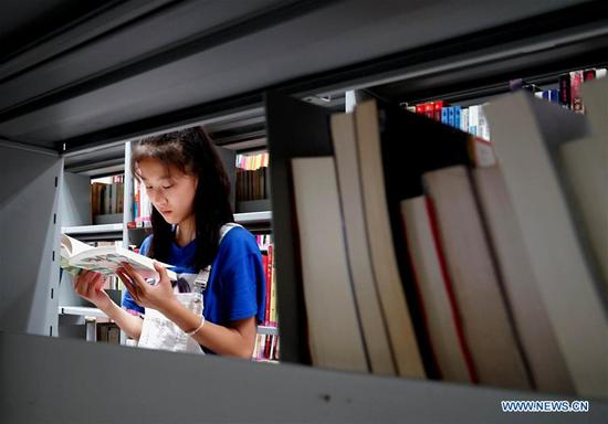 A girl reads books in Zhengzhou library in Zhengzhou, capital of central China's Henan Province, July 31, 2018. The library is packed with readers during the summer vacation. (Xinhua/Li An)