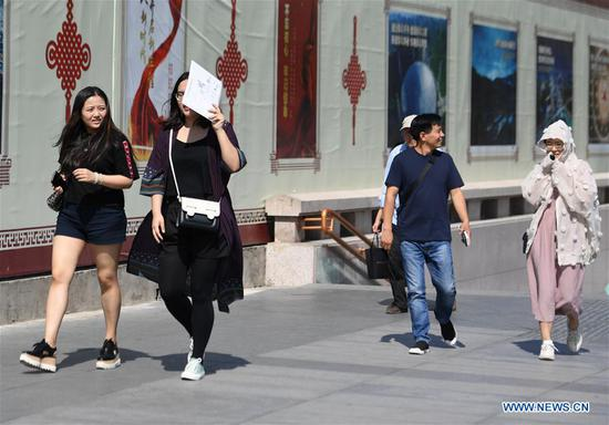 A pedestrian (2nd L) uses a personal item as sun shade in Beijing, capital of China, Beijing's observatory issued a yellow alert on Tuesday for high temperatures over the next four days. Temperature could rise to 35 degrees Celsius from Wednesday to Saturday, and reach up to 37 degrees Celsius on Thursday. (Xinhua/Zhang Chenlin)