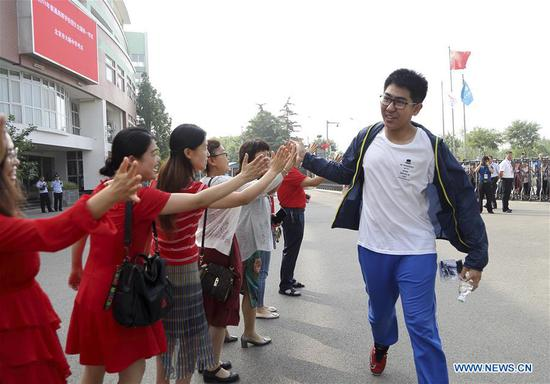138125574_15599521924031nTeachers cheer for an examinee at an exam venue at the Dayu Middle School in Beijing, capital of China, June 7, 2019. China's national college entrance examination, or Gaokao, started Friday this year. (Xinhua/Hou Jiqing)
