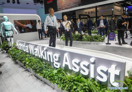 A visitor experiences Honda Walking Assist at the Automobile exhibition area during the second China International Import Expo (CIIE) in Shanghai, east China, Nov. 6, 2019. The National Exhibition and Convention Center in Shanghai greeted a large number of visitors on the second day of the CIIE. (Xinhua/Ding Ting)