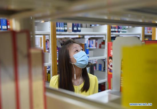 A reader searches books at the National Library of China in Beijing, capital of China, May 12, 2020. The southern area of the National Library of China reopened to the public on Tuesday. Visitors need to make reservations via the social media application Wechat or phone calls, according to a notice from the library. (Xinhua/Chen Zhonghao)