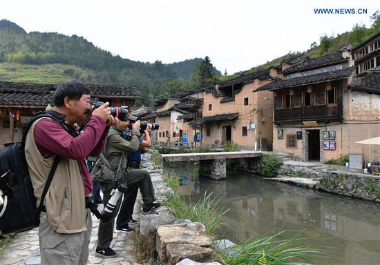 People take photos in Longtan Village of Pingnan County in Ningde City, southeast China's Fujian Province, Oct. 21, 2020. Longtan Village had been a provincial-level poverty-stricken village due to lack of arable land. Villagers went out for work one after another with many old buildings left in disrepair. In 2017, the county government launched a project to boost ancient villages through cultural and creative industries. The old houses, once forgotten, have been connected to public utilities, reinforced and decorated inside, with the ancient appearance of the village remained. Moreover, the renaissance here has attracted many people and college graduates outside the village to work here. Nowadays, more and more people come to visit Longtan since the village has become popular on the Internet. (Xinhua/Wei Peiquan)