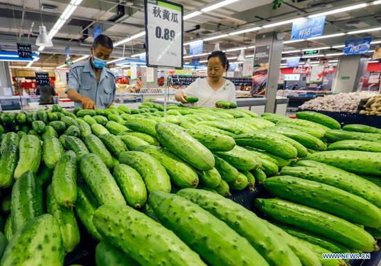A citizen buys cucumbers at a supermarket in Zunhua City, north China's Hebei Province, June 9, 2021. China's consumer price index (CPI), a main gauge of inflation, rose 1.3 percent year on year in May, data from the National Bureau of Statistics showed Wednesday. (Photo by Liu Mancang/Xinhua)