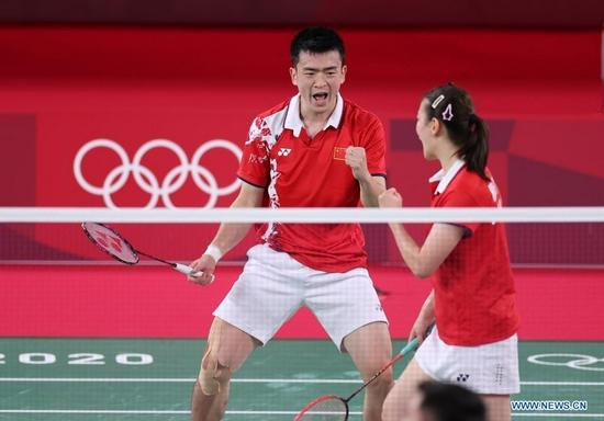 Zheng Siwei (L)/Huang Yaqiong of China react during the badminton mixed doubles semifinal between Zheng Siwei/Huang Yaqiong of China and Tang Chun Man/Tse Ying Suet of Hong Kong of China at the Tokyo 2020 Olympic Games in Tokyo, Japan, July 29, 2021. (Xinhua/Yang Lei)