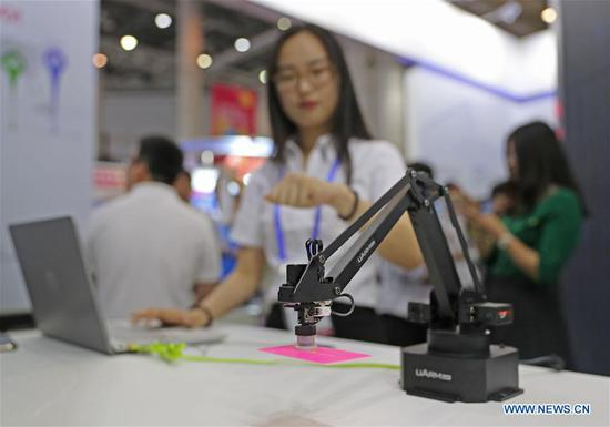 A woman manipulates mechanical arms through 5G technology during the 16th China International Software & Information Service Fair in Dalian, northeast China's Liaoning Province, June 12, 2018. The service fair, with the participation of 750 exhibitors, kicked off here Tuesday. (Xinhua/Yang Qing)
