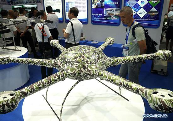 Visitors look at the latest drone at China International Industry Fair 2018 in east China's Shanghai, Sept. 19, 2018. The 20th China International Industry Fair opened Wednesday in Shanghai, with over 2,600 companies participating in the five-day event. (Xinhua/Chen Fei)
