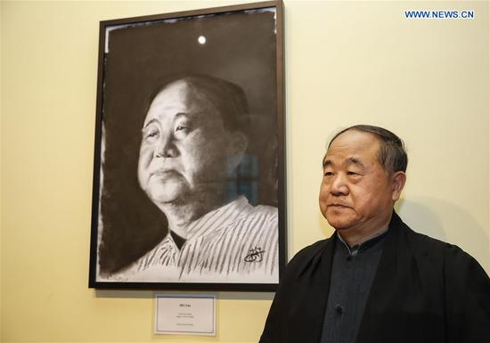Chinese writer and Nobel laureate Mo Yan poses with a portrait of himself after the Honorary Fellowship Recognition Ceremony at University of Oxford, Britain, on June 12, 2019. Mo Yan was awarded Wednesday the Honorary Fellowship by Regent's Park College, University of Oxford, in recognition of his contribution to Chinese and world literature. The college principal Robert Ellis presented the gown and stole to Mo at the ceremony. They unveiled together a new international writing center named after Mo. (Xinhua/Han Yan)