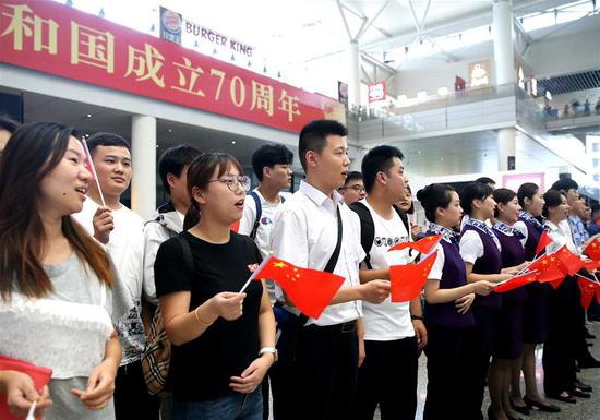 Passengers and staff members of Shanghai Hongqiao Railway Station take part in a flash mob in east China's Shanghai, Sept. 17, 2019. Participants chorused patriotic songs during the flash mob as a way to celebrate the 70th anniversary of the founding of the People's Republic of China. (Xinhua/Chen Fei)