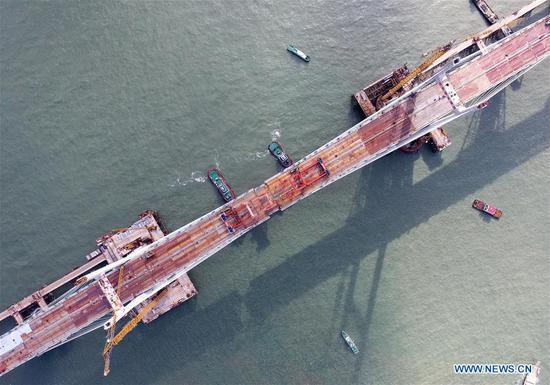 Aerial photo taken on Sept. 21, 2019 shows a steel girder being lifted by a crane at the construction site of the Pingtan Strait Road-rail Bridge in southeast China's Fujian Province. China on Wednesday completed the main structure of the world's longest cross-sea road-rail bridge in Fujian. The last steel girder, weighing 473 tonnes, was bolted on the Pingtan Strait Road-rail Bridge, another mega project in China, on Wednesday morning. With a staggering span of 16.34 km, the bridge connects Pingtan Island and four nearby islets to the mainland of Fujian Province. (Xinhua/Lin Shanchuan)
