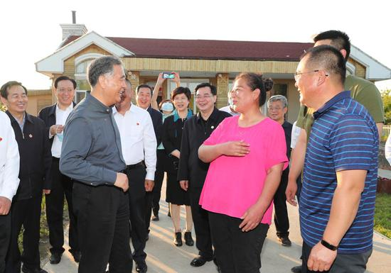 Wang Yang, a member of the Standing Committee of the Political Bureau of the Communist Party of China (CPC) Central Committee and chairman of the Chinese People's Political Consultative Conference (CPPCC) National Committee, talks with villagers at a Hezhe minority village in Fuyuan City during an inspection tour in northeastern Heilongjiang Province, June 8, 2021. Wang and 13 non-CPC members of the CPPCC National Committee inspected Heilongjiang from June 6 to 9. Wang stressed the importance of developing border areas and improving local people's lives during the inspection tour. (Xinhua/Yao Dawei)