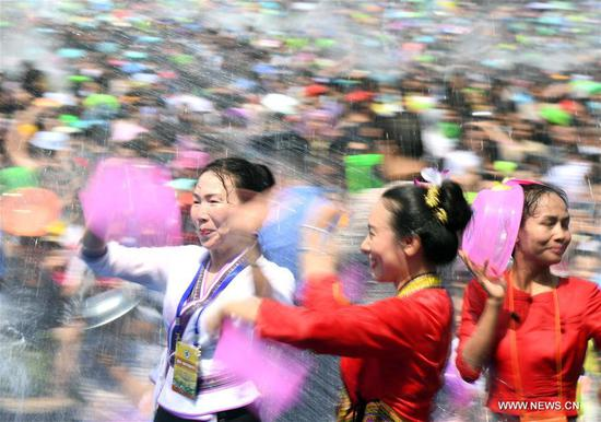 People celebrate the water-sprinkling festival at a square in Jinghong City, Dai Autonomous Prefecture of Xishuangbanna, southwest China's Yunnan Province, April 15, 2018. People sprinkle water to each other to pray for good fortune during the traditional water-sprinkling festival, which is also the New Year festival of the Dai ethnic group. (Xinhua/Wang Changshan)