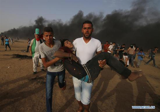 Palestinian protesters carry a wounded person during clashes with Israeli troops near the Gaza-Israel border, east of Khan Younis, southern Gaza Strip, on May 25, 2018. At least 25 Palestinian protesters were injured on Friday during clashes with Israeli soldiers along Gaza's eastern border with Israel, the health ministry in Gaza said. (Xinhua/Khaled Omar)