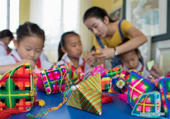 Pupils make sachets in the shape of Zongzi, pyramid-shaped dumplings made of glutinous rice wrapped in bamboo or reed leaves, to greet the upcoming Dragon Boat Festival at a primary school in Hohhot, capital of north China's Inner Mongolia Autonomous Region, June 12, 2018. (Xinhua/Ding Genhou)