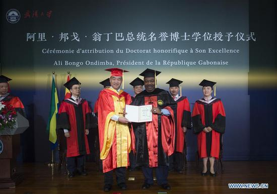 Dou Xiankang, president of Wuhan University, confers on Gabonese President Ali Bongo Ondimba (R, front) an honorary doctorate in law at the university in Wuhan, central China's Hubei Province, Sept. 6, 2018. Gabonese President Ali Bongo Ondimba has been conferred an honorary doctorate in law by the elite Wuhan University during his visit to central China's Hubei Province. (Xinhua/Xiao Yijiu)