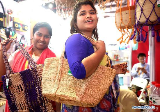 Staff members from Dada Bangla Limited present bags at the first China International Import Expo (CIIE) in Shanghai, east China, Nov. 6, 2018. More than 3,000 companies from over 130 countries and regions attended the CIIE. (Xinhua/Chen Fei)