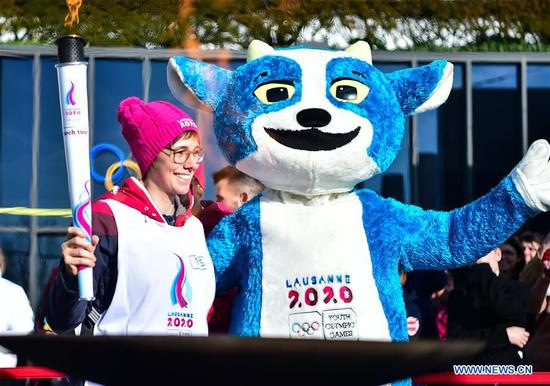Torch bearer Linda Indergand (L) poses for photos with mascot of Lausanne 2020, Yodli, after lighting up the cauldron during a torch relay for the 3rd Youth Winter Olympic Games in Lausanne, Switzerland, Jan. 8, 2020. (Xinhua/Lu Yang)