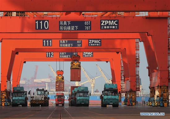 Containers are loaded onto trucks at Jingtang port area of Tangshan Port, north China's Hebei Province, July 8, 2018. The throughput of Tangshan Port reached 303 million tons from January to June this year, growing 7.28 percent year on year. (Xinhua/Yang Shiyao)