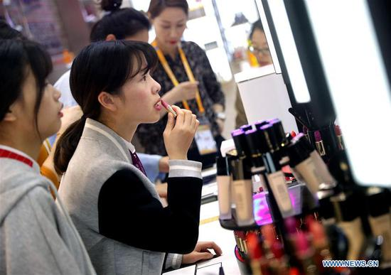 A visitor tries on makeup at the booth of L'Oreal at the first China International Import Expo (CIIE) in Shanghai, east China, Nov. 6, 2018. More than 3,000 companies from over 130 countries and regions attended the CIIE. (Xinhua/Chen Fei)